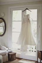 A wedding dress hanging in a window