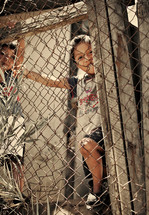 Children playing behind wire fence