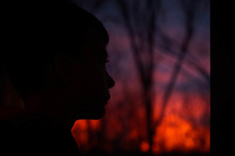 side profile silhouette of a boys face at sunset