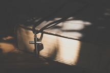 silver cross on a Bible in sunlight
