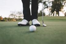 golfers feet on a putting green