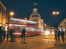 A red london bus driving through a city intersection at night