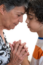 a grandmother praying with her grandson