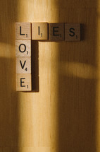 Scrabble tiles arranged to show how love is in the light and lies lead to shadows.