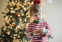 a toddler girl standing in front of a Christmas tree