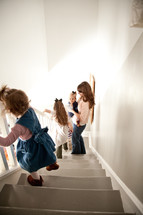 mother and children going down the stairs in their house.