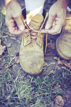 man tying boots outdoors.