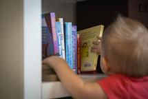 A toddler getting a book off of a bookshelf.