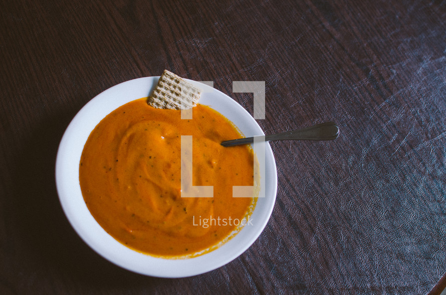 White bowl with orange soup with a cracker and spoon on a table