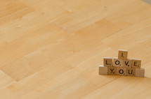 """I love you"" spelled out in stacked scrabble letters."