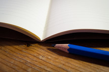 An open blank notebook with a blue pencil laying next to it on a wooden desk