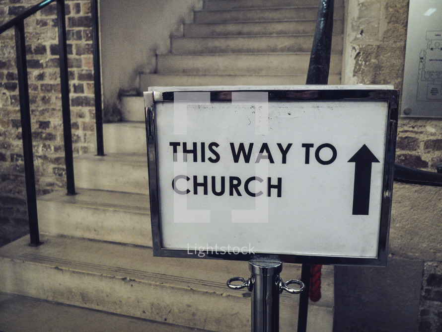A sign next to some stairs showing 'this way to church'