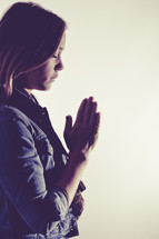 woman in prayer against a white background