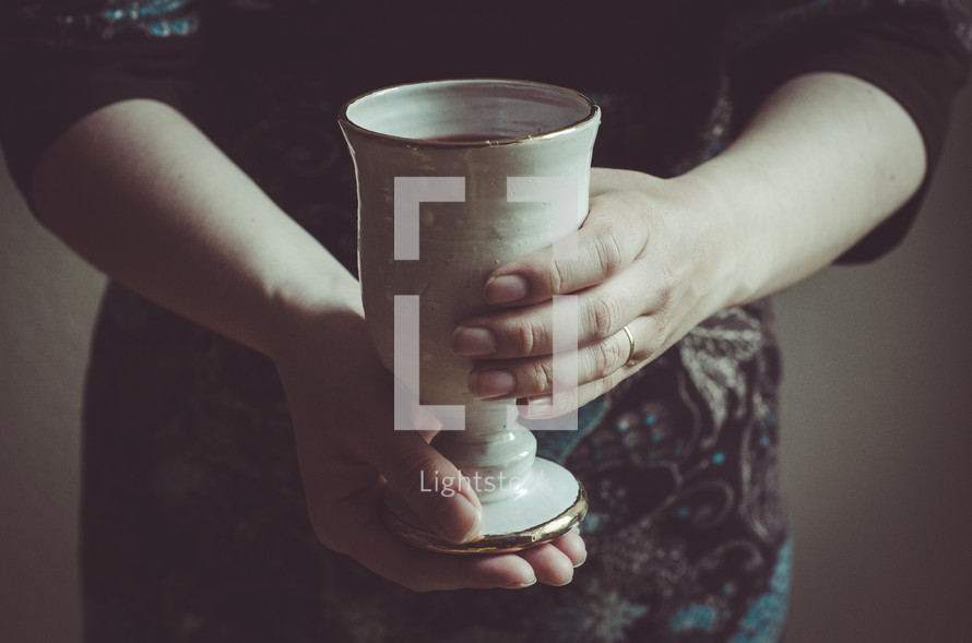 A woman holding a cup of communion wine.