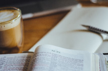 A coffee, notebook and a bible open to Acts on a table.