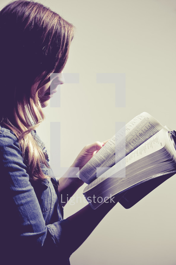 woman reading a Bible against a white background