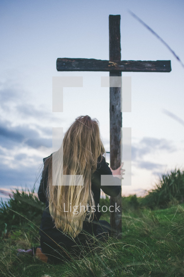 woman kneeling in front of a cross