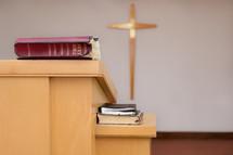 Bibles on the pulpit in front of a cross on the wall.