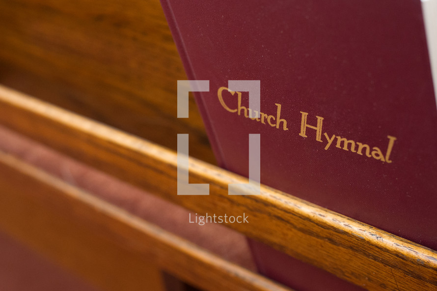 Hymnal on the back of a church pew.