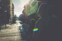 man in a hoodie walking down an alley in intense sunlight
