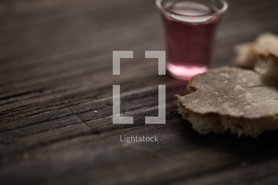 Communion bread and wine on a wood surface.