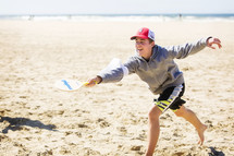 teen boy playing on a beach