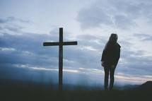 Silhouette of a persona standing by a cross in a field at sunrise.