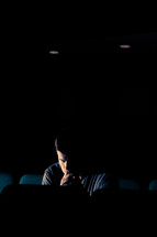 man sitting in an empty auditorium with his head bowed in prayer