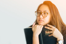 a young woman holding a Bible and thinking