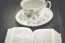 tea cup, saucer, and open Bible