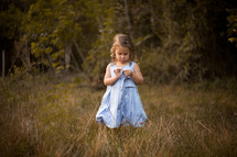 a toddler girl standing in tall grasses