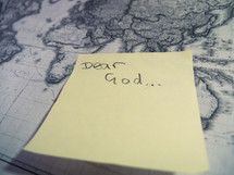 A post-it sticky note with 'Dear God' stuck to a an antique style map.