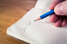 A male hand writing with a blue pencil in an open notebook with the words 'dear God'.