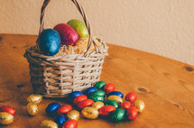 Colored easter eggs in a wicker basket on a wooden table