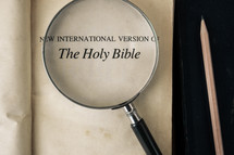 magnifying glass over Bible - The Holy Bible title page