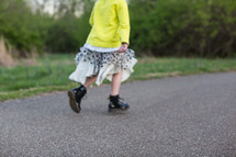 a girl child in boots and skirt stomping down a paved path