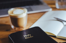 A coffee, bible, notebook and laptop on a table.