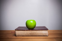 a green apple on a book on a desk