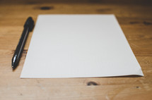 a pen and blank sheet of paper on a desk