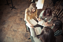 Women praying at a Bible study.