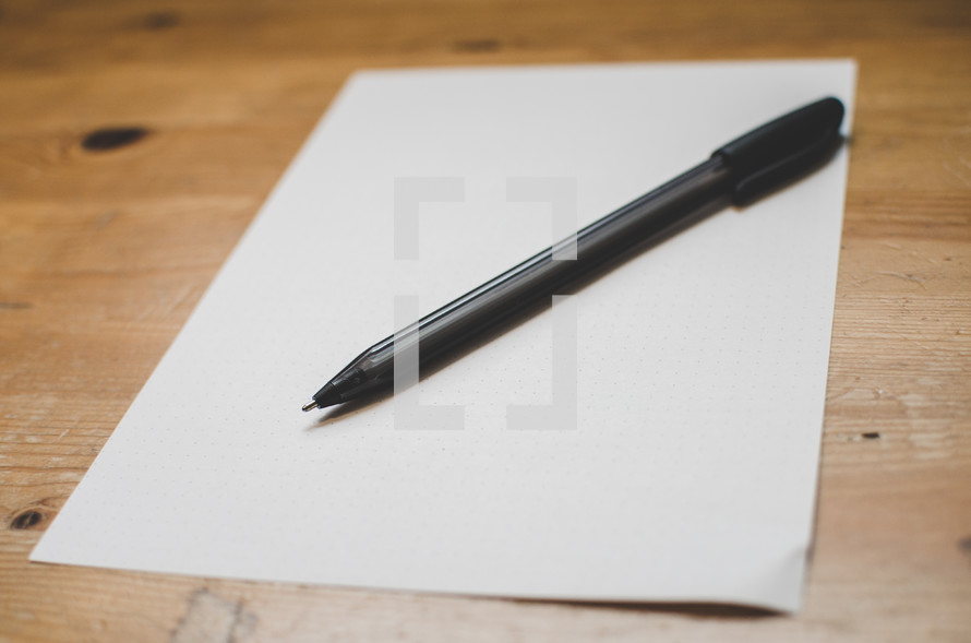 A blank piece of paper and pen on a writing desk