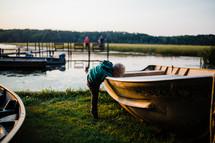 toddler exploring boats along a shore