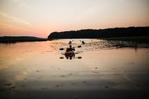 paddling kayaks at sunset