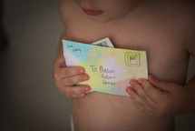 A young child holding a letter from his mother.