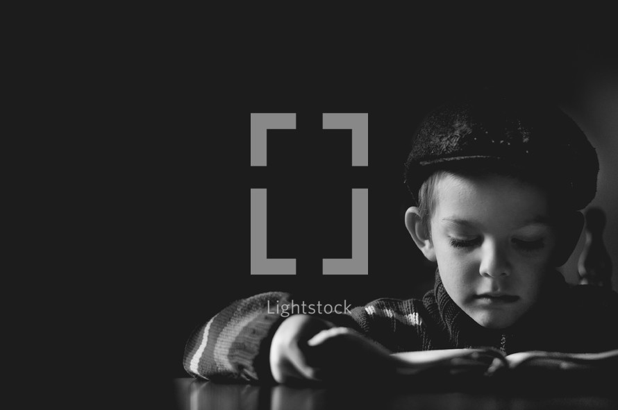 Boy with open bible reading the scriptures