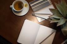 tea cup, sketch book and art pencils