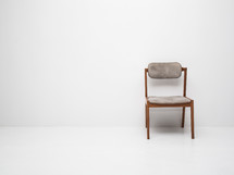 a single chair in an empty white room