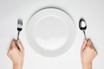plate and hands holding a fork and spoon
