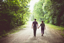 a couple walking holding hands on a dirt road