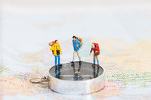 miniature figurines standing on a map and compass